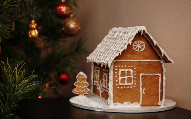 Gingerbread cinnamon house and decorated Christmas tree, in a dark juicy tone. Life style